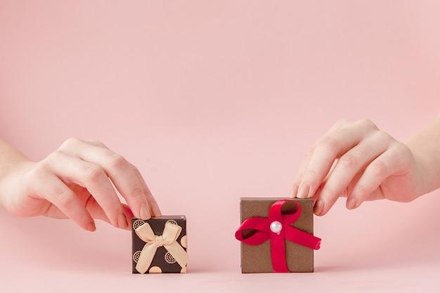 Piccole confezioni regalo nelle mani delle donne su uno sfondo rosa. concetto festivo per il giorno di san valentino