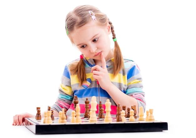 La piccola ragazza è concentrata quando gioca a scacchi