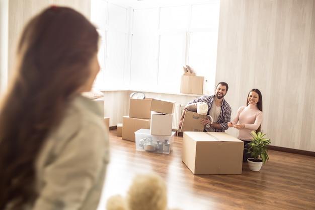 La piccola ragazza sta guardando ai suoi genitori. il giovane e la donna stanno disimballando le scatole per la loro nuova casa e stanno guardando alla loro figlia. le stanno sorridendo.