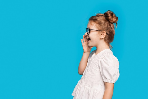 La piccola ragazza sta urlando su una parete blu dello studio con lo spazio libero con gli occhiali e il vestito bianco
