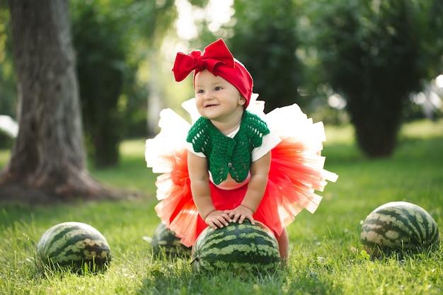 La piccola ragazza è seduta sull'erba verde con una gonna di tulle rossa con angurie.