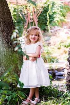 Piccola ragazza con lunghi capelli biondi e una faccia felice piuttosto sorridente in abito bianco da principessa del ballo