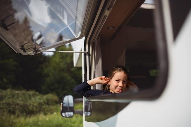 Piccola ragazza che guarda fuori attraverso la finestra della roulotte e fa i volti delle vacanze in famiglia