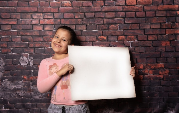 Piccola ragazza che fa pose con lettere di carta riciclata vuote davanti a un vecchio sfondo di muro di mattoni, sfondo scuro, messa a fuoco selettiva.