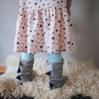 Le gambe della piccola ragazza in pantofole domestiche blu contro il muro
