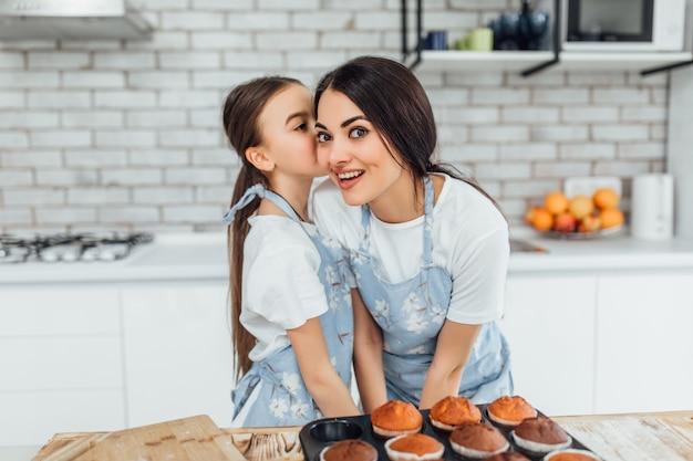 Piccola ragazza che dice un segreto a sua mamma in cucina