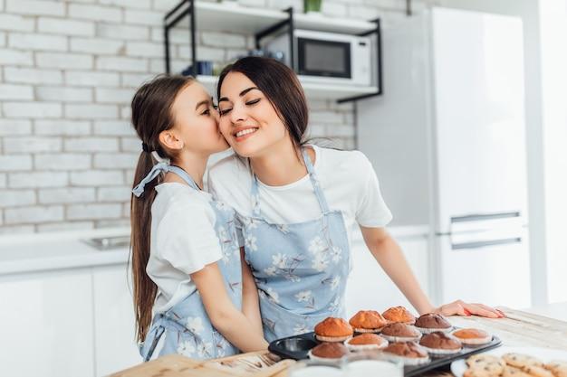 La bambina ha raccontato un segreto a sua mamma in cucina mentre cucinano