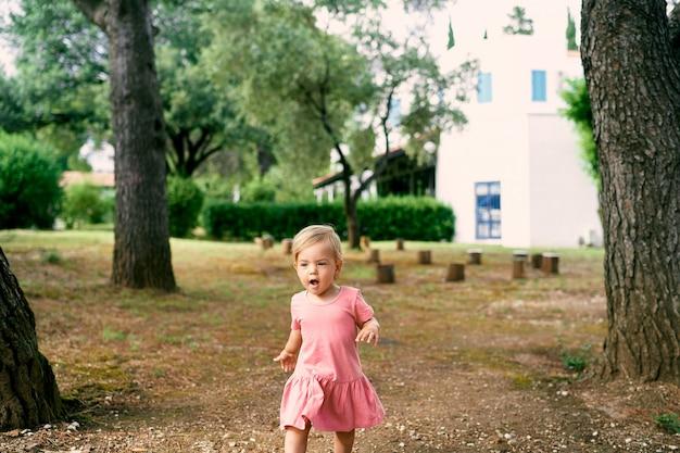 La piccola ragazza cammina con la bocca aperta in una radura vicino ai ceppi del cortile