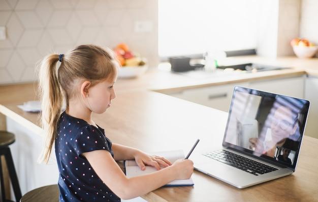 Piccola ragazza con laptop che impara tramite internet al chiuso a casa, virus corona e concetto di quarantena.