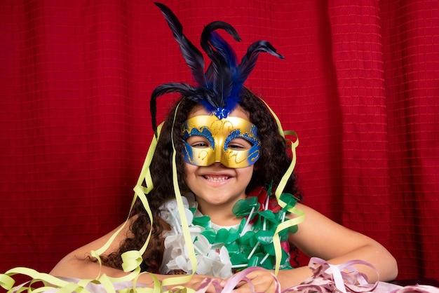 Piccola ragazza con maschera e collane usate nel carnevale brasiliano
