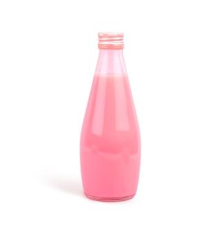 Piccola bottiglia di vetro con una bevanda al latte rosa su una parete bianca