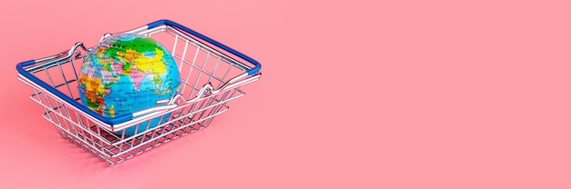 Piccolo globo in un cestino della spesa su sfondo rosa