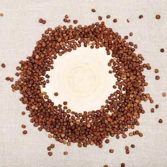 Piccoli chicchi di semi di fagioli di legumi a forma di cornice rotonda. piselli grigi e scrivania in legno.