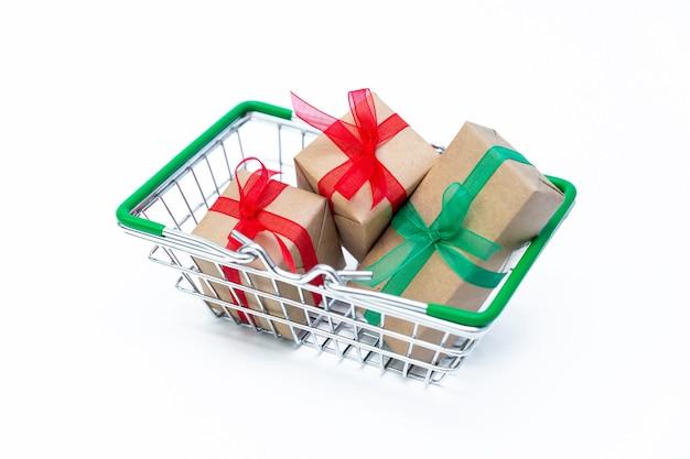 Piccolo cestino della drogheria con scatole regalo su superficie isolata bianca