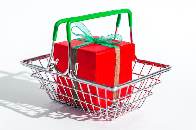 Piccolo cestino della drogheria con il contenitore di regalo rosso su spazio isolato bianco
