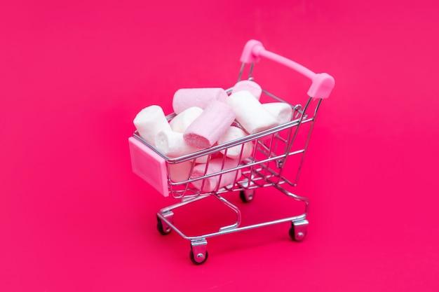 Piccolo carrello della spesa pieno di dolci caramelle marshmallow. fai regali con amore a san valentino
