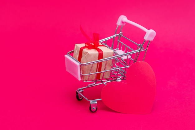 Piccolo carrello della spesa con scatole regalo. fai regali con amore a san valentino