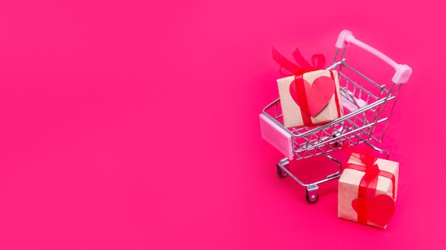 Piccolo carrello della spesa con scatole regalo su sfondo rosso-rosa. fai regali con amore a san valentino