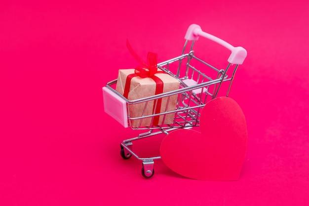 Piccolo carrello della spesa con scatole regalo sulla superficie rosso-rosa. fai regali con amore a san valentino