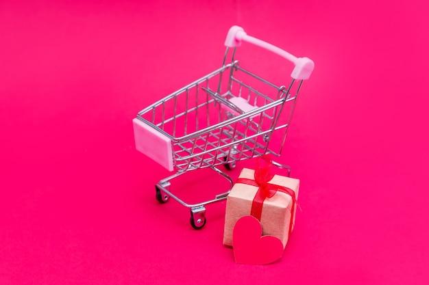Piccolo carrello della spesa con scatole regalo sulla superficie rosso-rosa
