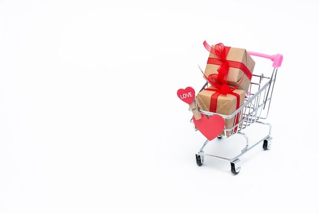 Piccolo carrello della spesa con scatole regalo su sfondo bianco. fai regali con amore a san valentino