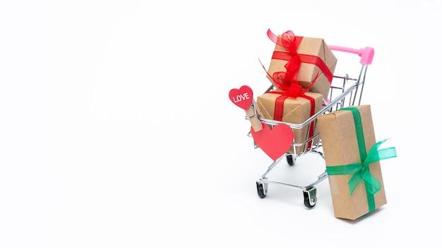 Piccolo carrello della spesa con scatole regalo sulla superficie bianca. fai regali con amore a san valentino