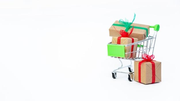 Piccolo carrello della spesa con scatole regalo sulla superficie bianca
