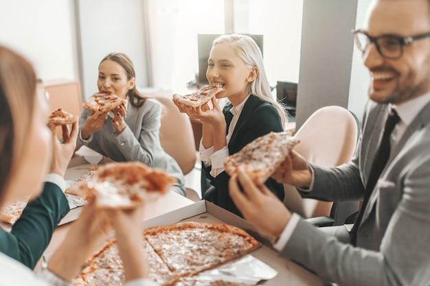 Piccolo gruppo di uomini d'affari in giacca e cravatta a pranzo insieme. messa a fuoco selettiva sulla donna bionda. la cosa bella del lavoro di squadra è che hai sempre gli altri dalla tua parte.