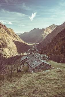 Piccolo gruppo di vecchie case di pietra tra la montagna e la foresta nelle alpi italiane. villaggio rurale nella valle, immagine tonica, filtro vintage.