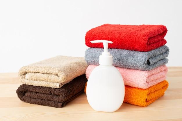 Piccoli asciugamani e bottiglia di sapone liquido sul tavolo