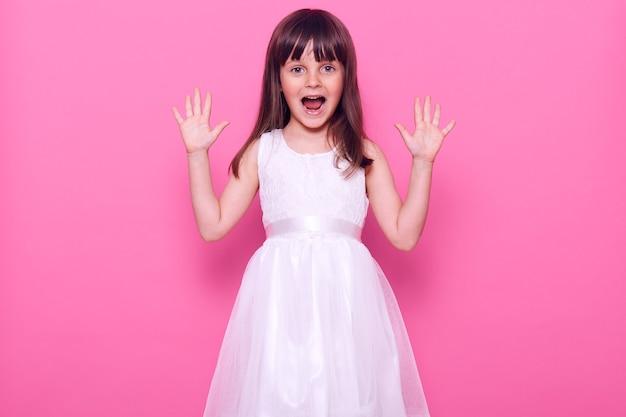 Piccola femmina dai capelli scuri felice in abito bianco guardando direttamente davanti e urlando allegramente, celebrando un evento positivo e tanto atteso, isolato sopra il muro rosa Foto Premium