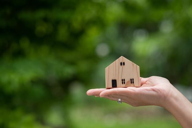 Piccolo modello di casa a portata di mano con sfondo bokeh, casa in miniatura