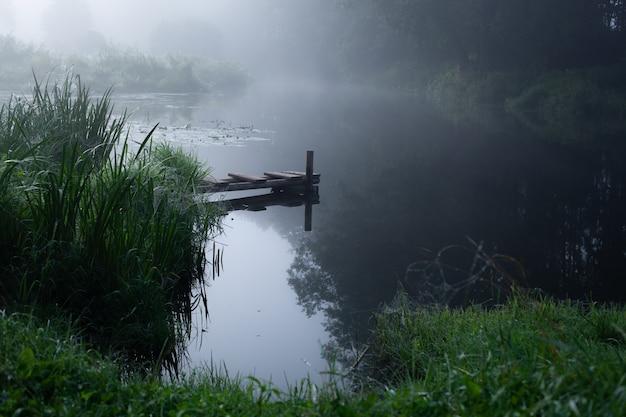 Piccolo molo fatto in casa nel villaggio per barche e pescatori sul fantastico fiume nebbioso all'alba