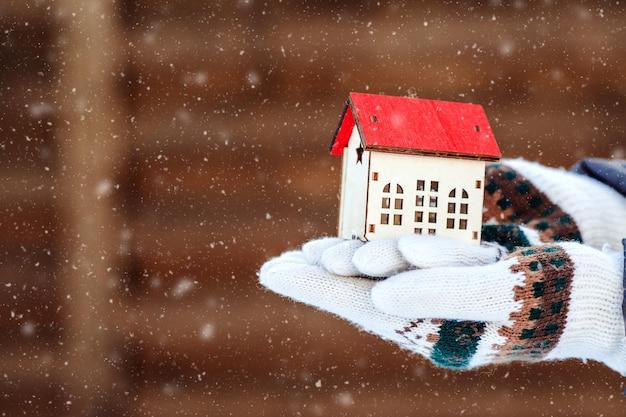 Piccola casa in mano su sfondo invernale. preparare la casa per l'inverno. concetto di bene immobile e proprietà.