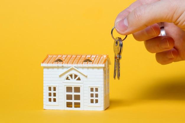 Piccola casa con le chiavi in mano su giallo
