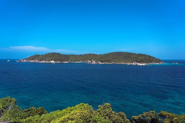 Una piccola isola in lontananza sullo sfondo del cielo azzurro e senega bellissimo mare trasparente. alberi verdi in primo piano.
