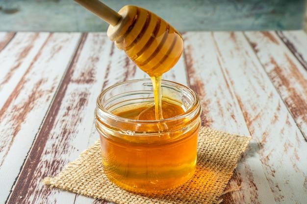 Piccolo vasetto con puro miele biologico di api con il bastoncino di miele caricato con il miele dal vaso su un tavolo rustico. Foto Premium