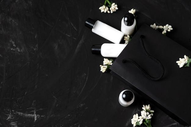 Piccoli vasetti con cosmetici in un sacchetto di carta nera e fiori su uno sfondo nero sconti di vendita