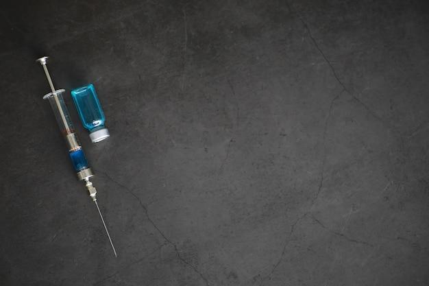 Piccoli vasetti con iniezione e siringa per iniezione su sfondo blu vicino alla formula chimica