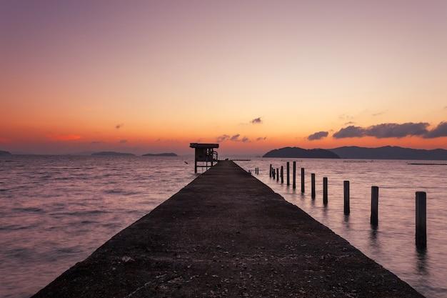 Piccolo molo al mare nell'immagine a lunga esposizione del tramonto o dell'alba, del cielo e delle nuvole drammatici