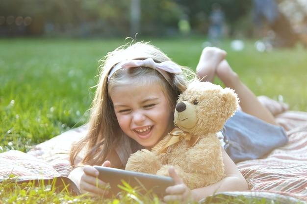Una bambina piccola che guarda nel suo telefono cellulare insieme al suo orsacchiotto preferito all'aperto nel parco estivo.