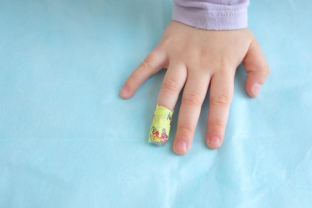 Bambino piccolo mano palmo dito bendato gesso esame medico del sangue in clinica ospedaliera analisi di laboratorio