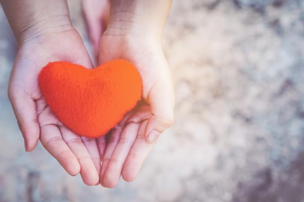 Piccole mani del bambino che tengono il cuore