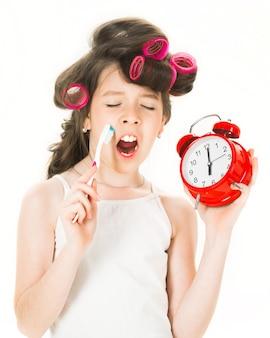 Piccola signora in pigiama. bambina la mattina, lavarsi i denti. bambina che tiene l'orologio