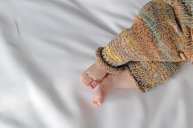 Piccole gambe del neonato in pantaloni di lana lavorata a maglia, primo piano, vista dall'alto