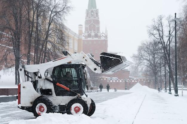 Un piccolo bobcat escavatore caricatore rimuove la neve dal marciapiede vicino alle mura del cremlino durante una forte nevicata.