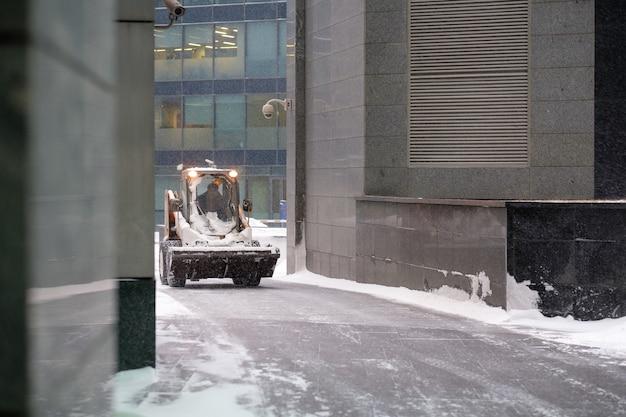 Un piccolo escavatore caricatore con una benna rimuove la neve da una strada su una strada cittadina durante una forte nevicata.