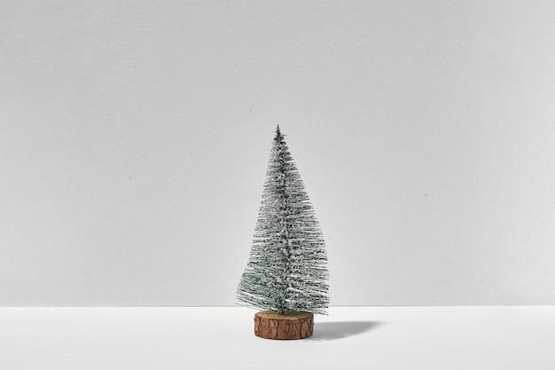 Piccolo albero di natale solitario su priorità bassa bianca con l'ombra della luce solare. quarantena natale
