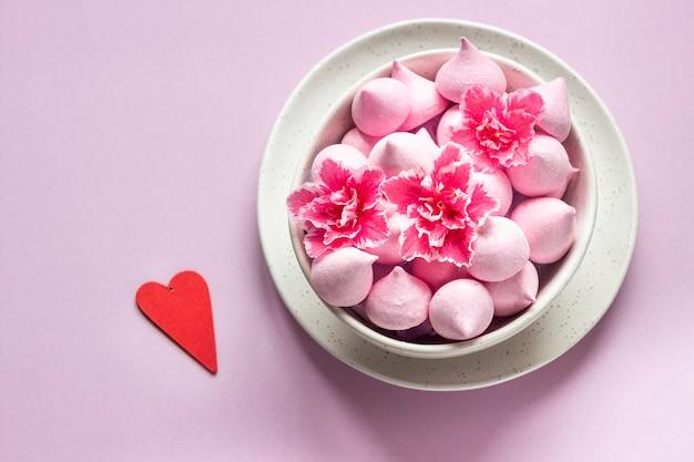 Piccole meringhe e fiori rosa in una ciotola di ceramica. regalo per san valentino.