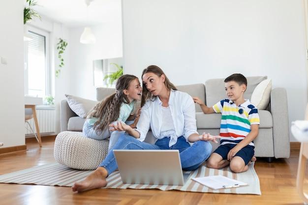 Piccoli bambini dispettosi che fanno rumore e distraggono la madre freelancer che cercano di concentrarsi sul laptop e stringono la testa lavorando al tavolo in un soggiorno luminoso